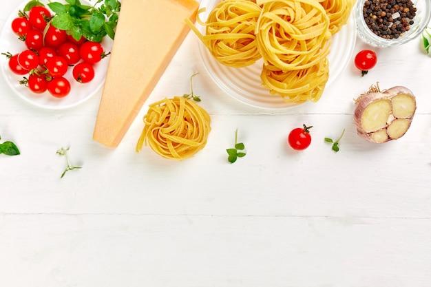 Zutaten zum kochen von pasta tagliatelle, tomaten, knoblauch, basilikum, parmesan