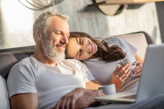 Zuverlässige schulter. glückliche junge frau, die kopf auf schulter des grauhaarigen lächelnden mannes berührt, der laptop im bett betrachtet