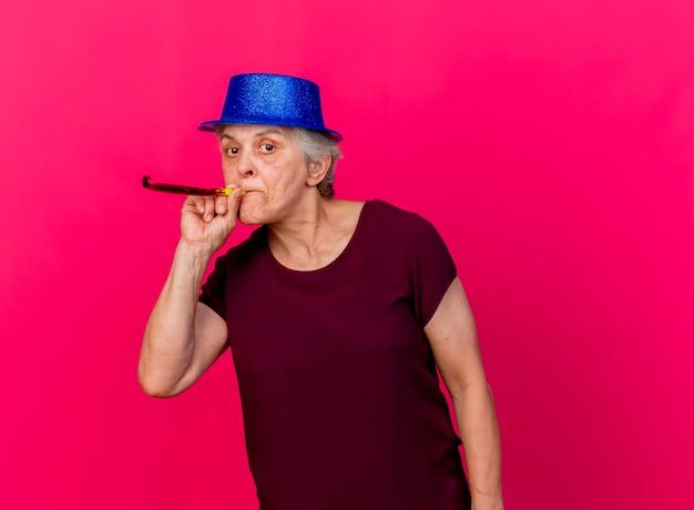 Zuversichtlich ältere frau, die partyhut bläst pfeife betrachtet kamera auf rosa