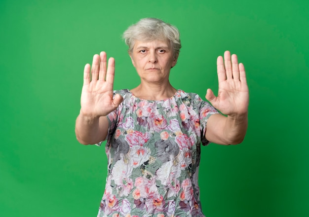 Zuversichtlich ältere frau gestikuliert handzeichen mit zwei händen lokalisiert auf grüner wand