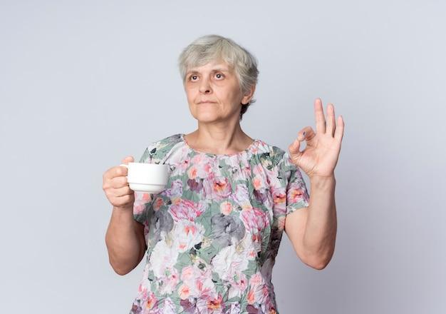 Zuversichtlich ältere frau hält tasse und gestikuliert ok handzeichen lokalisiert auf weißer wand