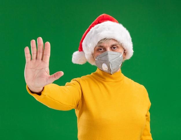 Zuversichtlich ältere frau mit weihnachtsmütze, die medizinische maske gestikulierendes stoppschild trägt, lokalisiert auf grünem hintergrund mit kopienraum