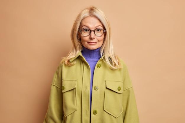 Zuversichtlich ältere lehrerin kleider für die arbeit hat blonde haare trägt transparente brille rollkragenpullover und stilvolle jacke gehen im herbst tag im freien spazieren gehen.