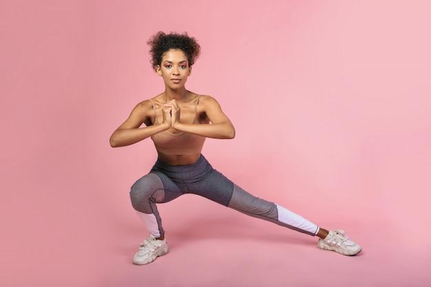 Zuversichtlich afroamerikanische frau, die übungen im studio über pivk hintergrund tut. stilvolles fitness-outfit.