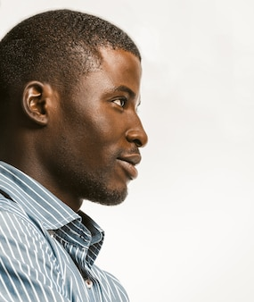 Zuversichtlich afroamerikanischer mann, der zart lächelt und die rechte seite mit textspace betrachtet. junger dunkelhäutiger geschäftsmann lokalisiert auf weißem hintergrund. profilansicht. nahaufnahme unten schuss. getöntes bild