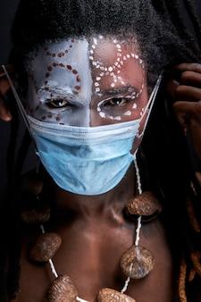 Zuversichtlich afroamerikanischer mann trägt medizinische schutzmaske auf gemaltem gesicht, lokalisiert über schwarzer studiowand. nackter mann mit dreadlocks halten sicher und gesund,