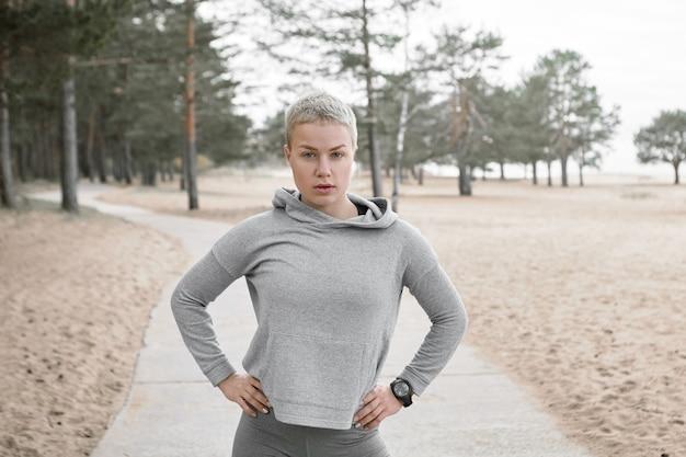 Zuversichtlich athletische blonde frau mit kurzer frisur, die draußen mit händen auf ihrer verschwendung posiert, die kleine pause während des cardio-trainings hat. attraktiver weiblicher läufer im stilvollen kleidertraining im park
