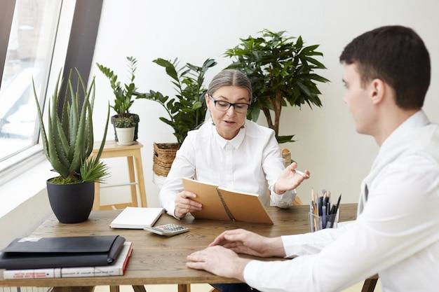 Zuversichtlich attraktiver weiblicher ceo in ihren fünfzigern, der heft hält und fragen zu berufsqualifikation, erfahrung und fähigkeiten während des interviews mit brünettem männlichem bewerber stellt. filmeffekt