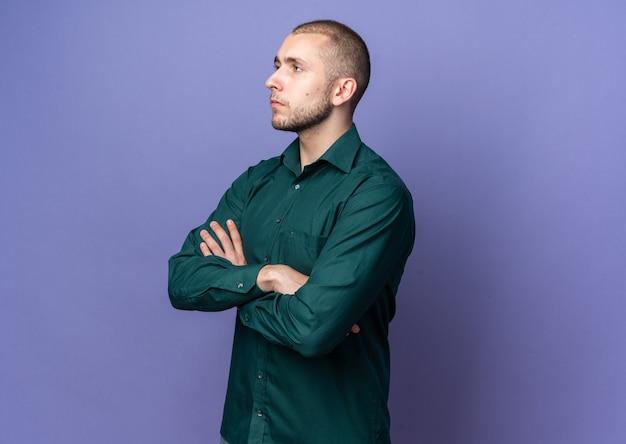 Zuversichtlich aussehender junger gutaussehender kerl, der grünes hemd trägt, das die hände kreuzt