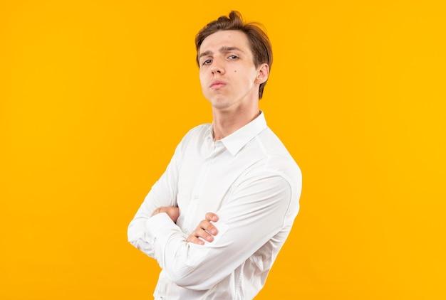 Zuversichtlich aussehender junger gutaussehender kerl der kamera, der weißes hemd trägt, das die hände kreuzt