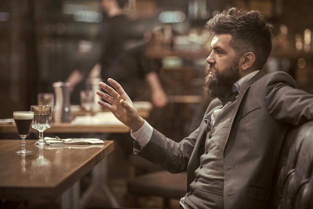 Zuversichtlich bar kunde sprechen im café. datum oder geschäftstreffen des hipsters in der kneipe. bärtiger mann im restaurant.