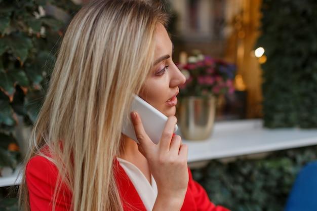 Zuversichtlich blonde geschäftsfrau in der roten stilvollen jacke, die durch mobyle telefon spricht und im stadtcafé sitzt