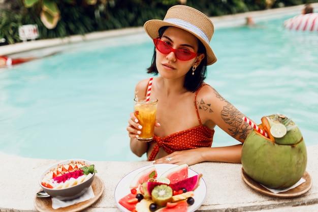 Zuversichtlich brünette bräune frau in roten katzenaugen sonnenbrille entspannen im pool mit platte von exotischen früchten während tropischer ferien. stilvolles tattoo.