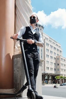 Zuversichtlich ehrgeiziger junger geschäftsmann in der sonnenbrille, die draußen mit roller steht