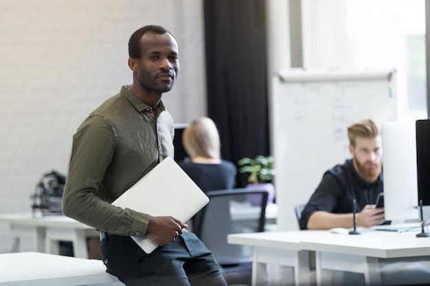 Zuversichtlich erfolgreicher afrikanischer mann, der auf einem schreibtisch mit laptop sitzt