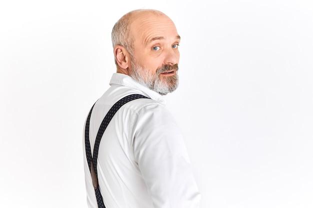 Zuversichtlich erfolgreicher europäischer mann im ruhestand im stilvollen weißen hemd und in den hosenträgern, die sich umdrehen und kamera mit ernstem gesichtsausdruck betrachten. konzept für menschen, alter, reife und eleganz