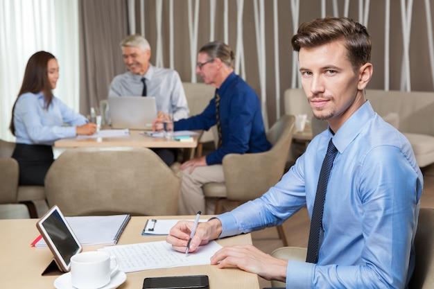Zuversichtlich erfolgreicher junger mann in cafe arbeiten