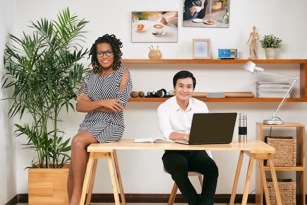 Zuversichtlich erfolgreiches junges multiethnisches geschäftsteam, das im modernen büro arbeitet