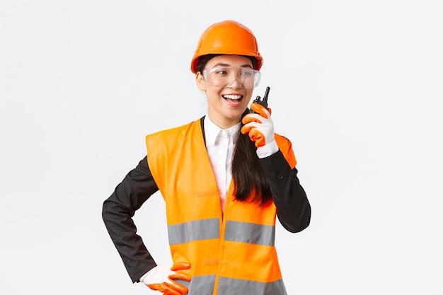 Zuversichtlich erfreute asiatische ingenieurin in schutzhelm und uniform, die mit dem chefarchitekten über walkie-talkie spricht. zufriedenes bautechniker-kontaktteam über funktelefon