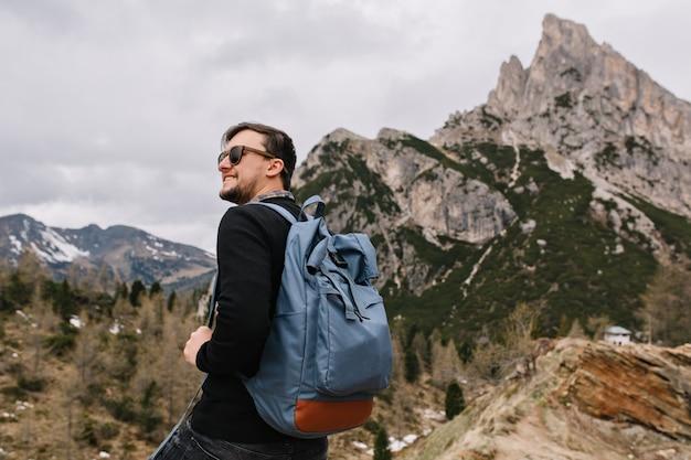 Zuversichtlich erfreuter mann mit dem lächeln, das in den himmel schaut und frische bergluft während der reise genießt