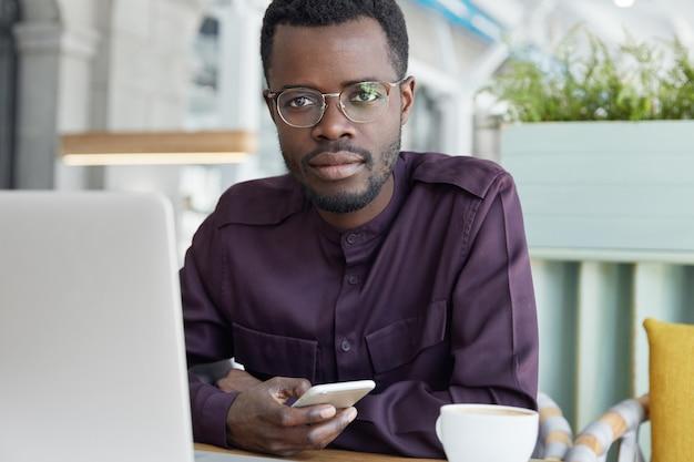 Zuversichtlich ernsthafte unternehmensangestellte typen nachricht auf smartphone, formell gekleidet, sitzt vor generischen laptop-computer