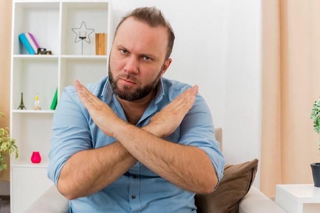 Zuversichtlich erwachsener slawischer mann sitzt auf sessel, der hände kreuzt und kein zeichen gestikuliert, das kamera im wohnzimmer betrachtet