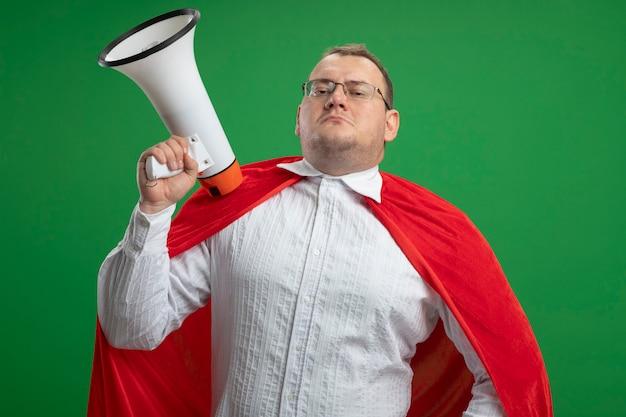 Zuversichtlich erwachsener slawischer superheldenmann im roten umhang, der brille hält, der lautsprecher lokalisiert auf grüner wand hält