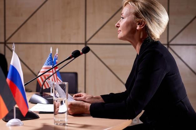 Zuversichtlich exekutive frau bei der politischen pressekonferenz, politische führerfrau, die im sitzungssaal ins mikrofon spricht. geschäft, menschen konzept