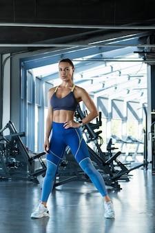 Zuversichtlich fitte brünette in sportkleidung posiert im fitnessstudio