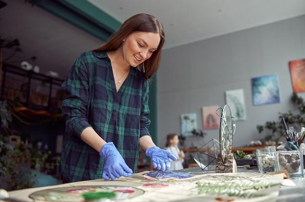 Zuversichtlich floristin arbeitet mit getrockneten blumen in gemütlichen blumenladen