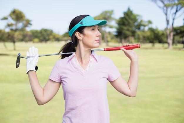 Zuversichtlich frau, die golfschläger trägt