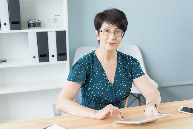 Zuversichtlich frau mittleren alters arbeitet mit tablette im büro