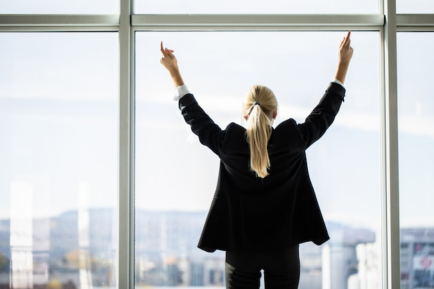Zuversichtlich geschäftsfrau, die hände ausbreitet, die am bürofenster stehen, große stadt genießen, erfolgreicher unternehmer, der geschäftserfolg mit weit geöffneten armen feiert, sich kraftvoll inspiriert fühlt, rückansicht