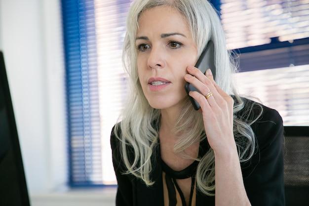 Zuversichtlich geschäftsfrau, die über telefon im büroraum spricht und etwas ansieht. nahaufnahmeporträt des ceo, der projekt auf smartphone bespricht. geschäfts-, kommunikations- und top-management-konzept