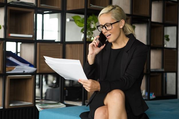 Zuversichtlich geschäftsfrau diskutieren papiere am telefon