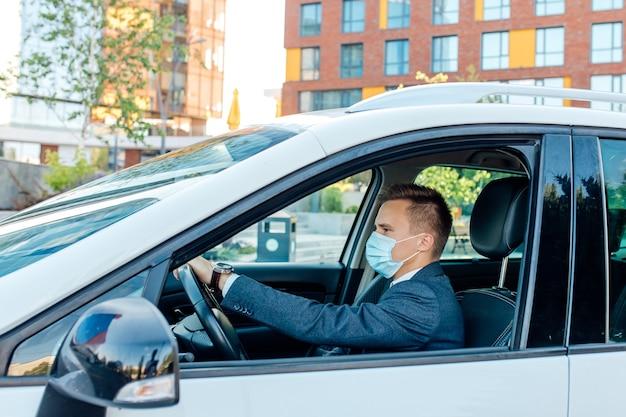 Zuversichtlich geschäftsmann in der medizinischen maske, die auto in der stadt fährt