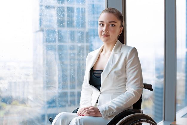 Zuversichtlich glückliche geschäftsfrau im rollstuhl vor dem hintergrund eines panoramafensters mit blick auf die wolkenkratzer und eine große stadt, lächelt sie in die kamera, behinderung überwindung konzept