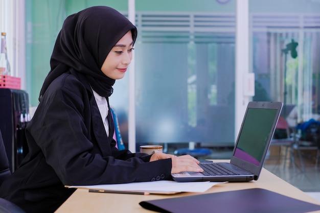 Zuversichtlich glückliche junge geschäftsfrau, die am schreibtisch arbeitet, der am computer arbeitet
