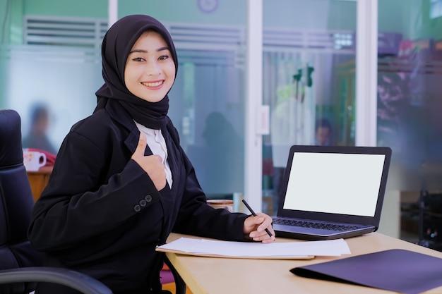 Zuversichtlich glückliche junge geschäftsfrau, die am schreibtisch sitzt