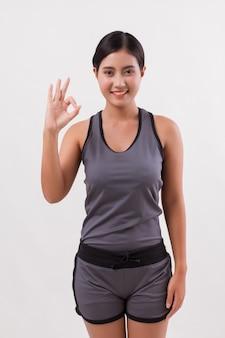 Zuversichtlich glückliche lächelnde fitnessfrau, die ok handgeste gibt