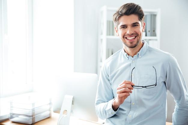 Zuversichtlich glücklicher geschäftsmann, der im büro steht und eine brille hält