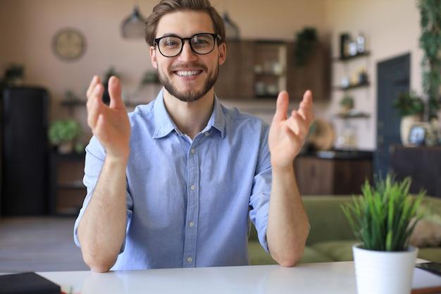 Zuversichtlich glücklicher geschäftsmann in brillen, der zu hause am arbeitsplatz sitzt und in die kamera schaut.