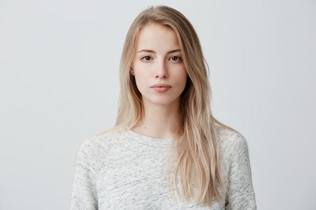 Zuversichtlich gut aussehende schöne frau mit blond gefärbtem haar gekleidet in freizeitkleidung, die ernsthaft schaut