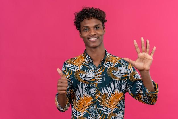 Zuversichtlich gut aussehender dunkelhäutiger mann mit lockigem haar im blatt bedruckten hemd, das nummer sechs mit den händen zeigt