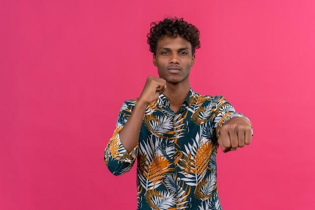 Zuversichtlich gut aussehender dunkelhäutiger mann mit lockigem haar in blättern bedrucktes hemd übt boxbewegungen während