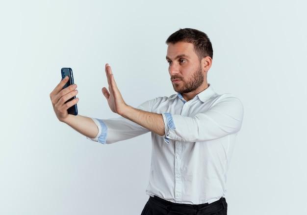 Zuversichtlich gutaussehende manngesten stoppen handzeichen, das telefon lokalisiert auf weißer wand hält und betrachtet