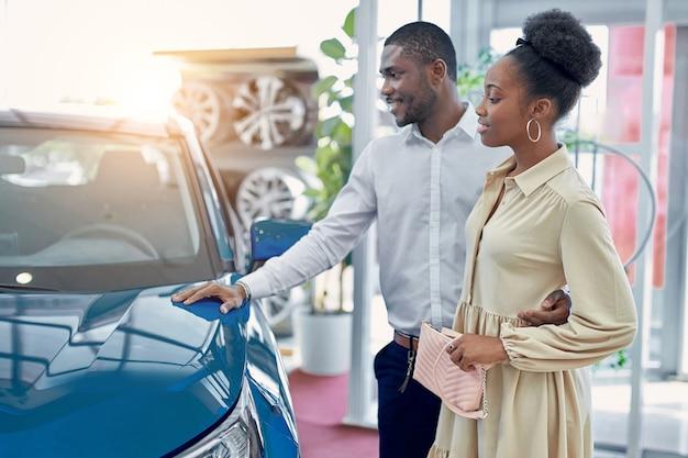 Zuversichtlich gutaussehender afro-mann zeigt frau ein auto, das er mag, sie schauen sich auto an und diskutieren