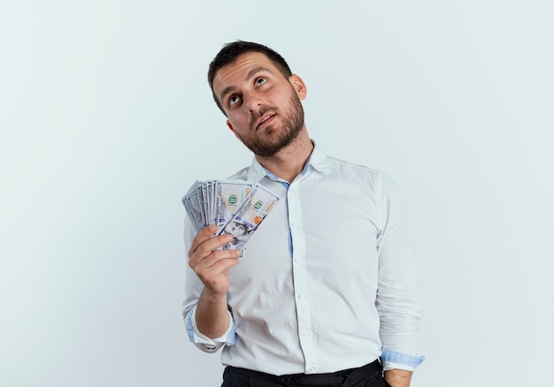 Zuversichtlich gutaussehender mann hält geld, das lokal auf weißer wand schaut