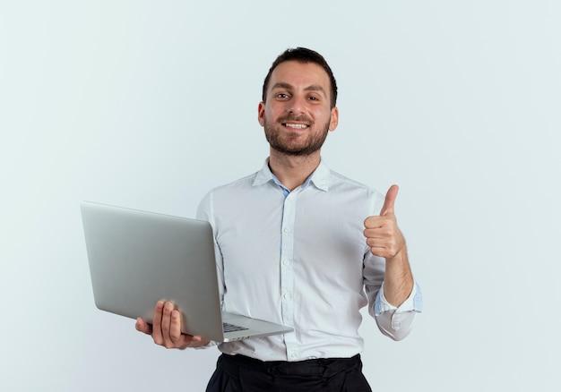 Zuversichtlich gutaussehender mann hält laptop daumen hoch isoliert auf weißer wand