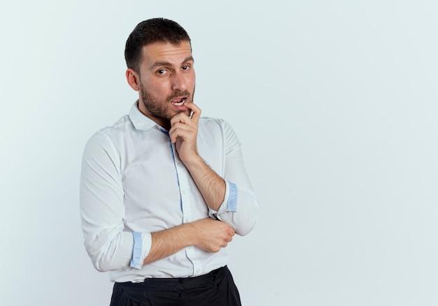 Zuversichtlich gutaussehender mann legt finger auf mund, der auf weißer wand isoliert schaut